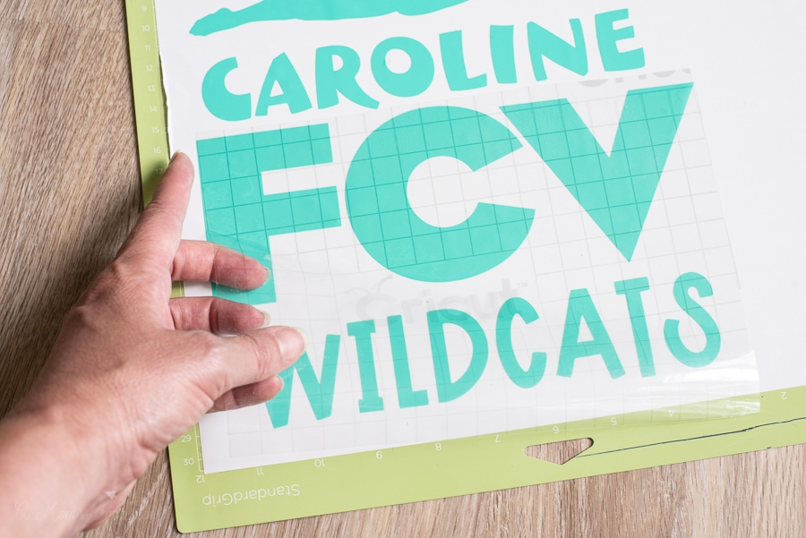a person weeding out vinyl from a design that says FCV