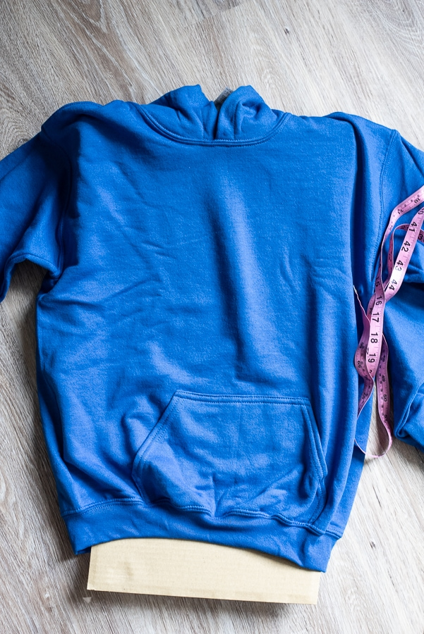 a blue hoodie with a pink tape measure