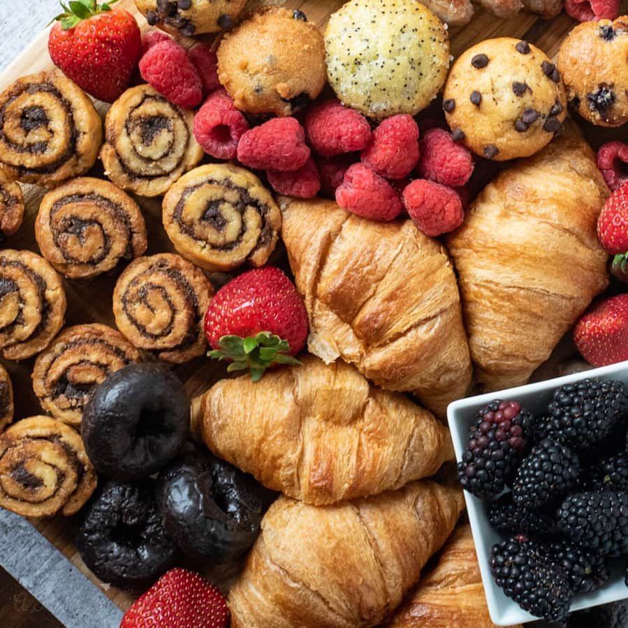 a lot of breakfast foods and fruit displayed on a cutting board