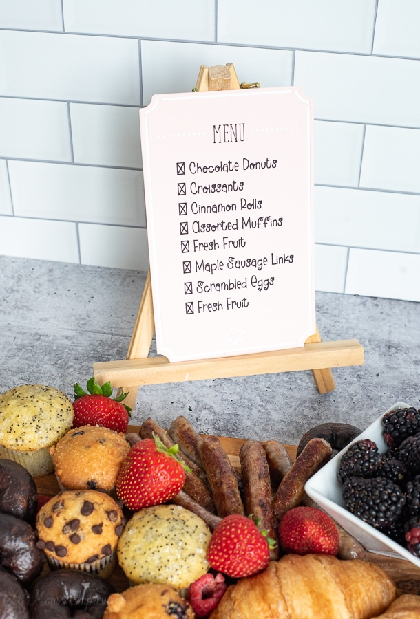 a menu being displayed behind a charcuterie board