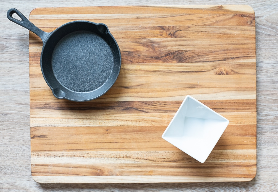 a small cast iron pan and a bowl on a cutting board