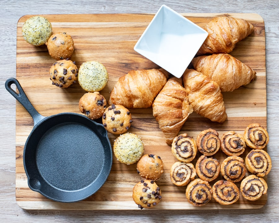 muffins, cinnamon rolls, and croissants on a cutting board