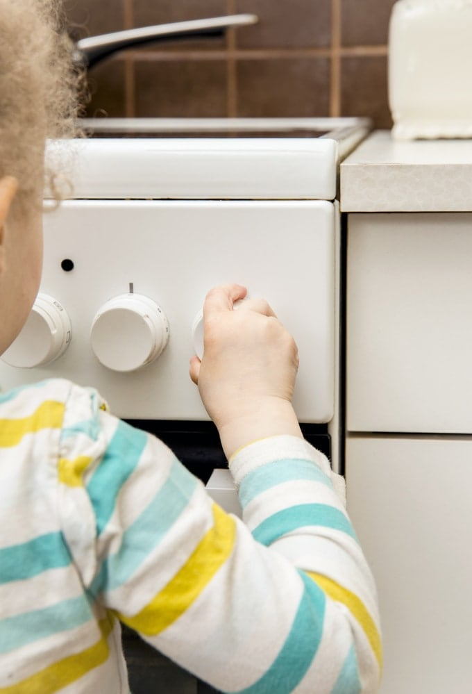 A child trying to turn on the oven