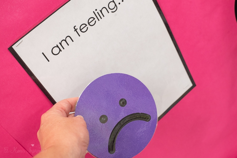 a purple frowny face being placed on a board that says I am feeling...