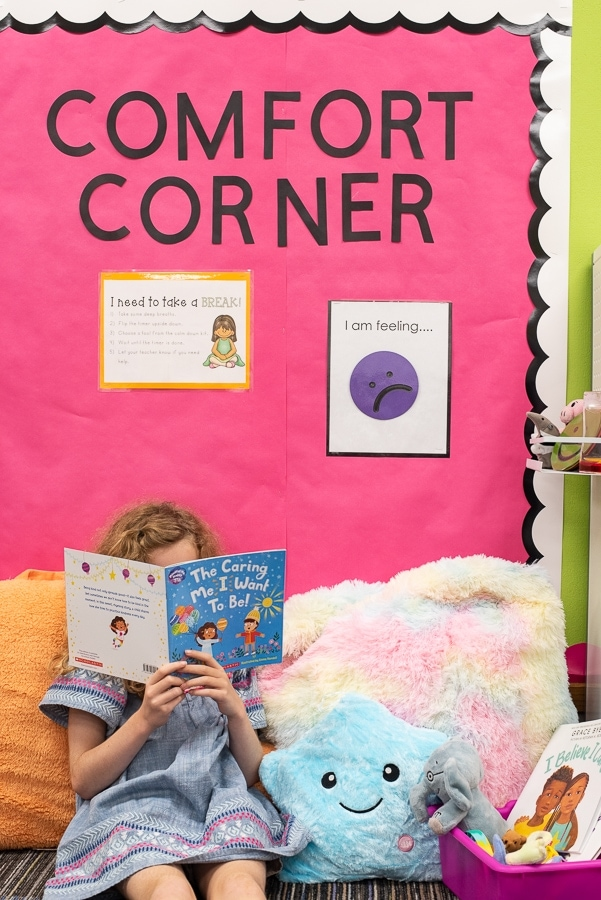 a girl reading a book sitting on pillows in a calming corner